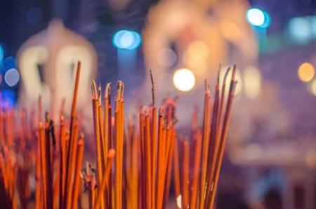 Red incense sticks burning in bokeh night photo