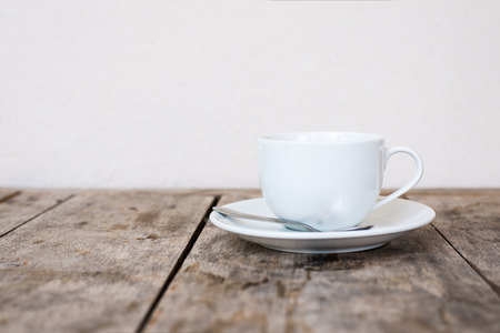 White cup on wood table