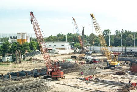 contruction: Crane operating among metal foundation poles