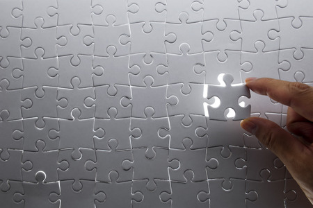 jigsaw pieces: puzzle piece coming down into its place Stock Photo