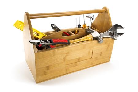 Boîte à outils en bois avec des outils isolé sur blanc Banque d'images