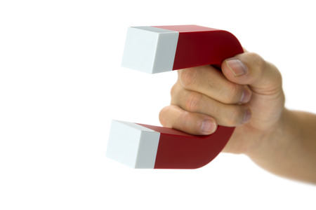 magnet: A hand holding a magnet isolated on white to pick up an object