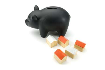 house exchange: piggy bank and little house isolated on white background Stock Photo