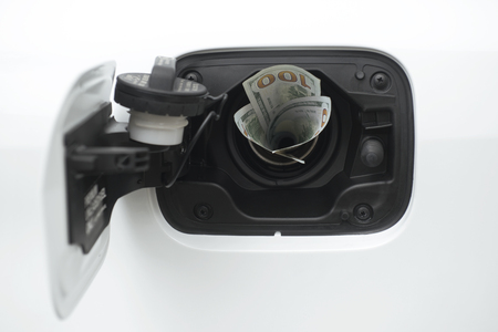 natural gas prices: One hundred dollars USD worth of twenty dollar bills sticking out of a car gas cap. Stock Photo