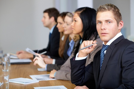 Team of 5 business people sitting at conference table with young businessman on the foreground Stock Photo - 11274286