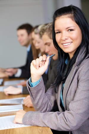 Team of 5 business people sitting at conference table with young businesswoman on the foreground photo