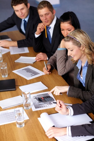 Team of 5 business people working on some calculations, calculator and come documents on conference table Stock Photo - 11274350