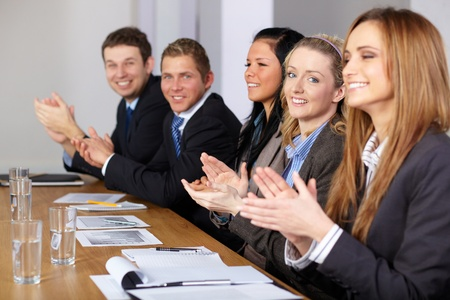 Business team clapping hands during theri meeting, focus on blonde smiling female Archivio Fotografico
