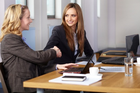 Welcome handshake before business meeting, young blonde and brunette businesswoman sitting at conference table