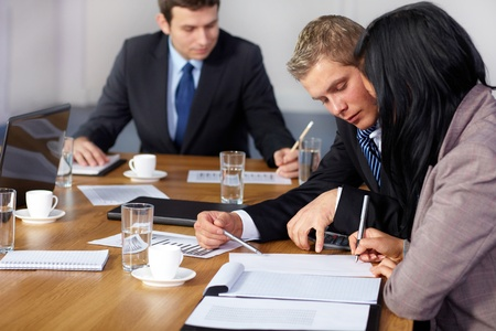 Team of 3 business people working on some calculations, calculator and some documents on table Stock Photo - 11274321