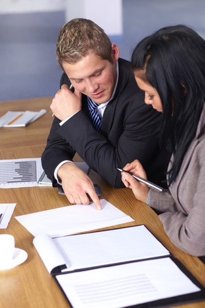 Team of 2 business people working on some documents, calculator and some documents on conference table Stock Photo - 11274329