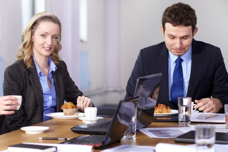 Young businessman and businesswoman sitting at conference table have a break during meeting photo