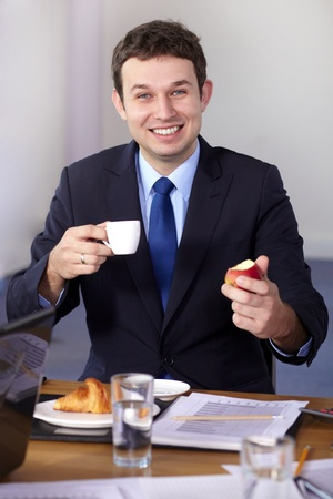 Young businessman sitting at conference table have a break during meeting, holds coffee cup and apple photo