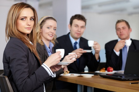 Business team having a coffee break during their meeting, all hold small coffee cups photo