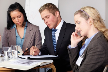Team of 3 business people working on some documents, one female talks over mobile phone Stock Photo - 11274326