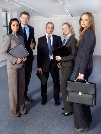 Group of 5 young business people, 3 females and 2 males all confident and looking to camera photo