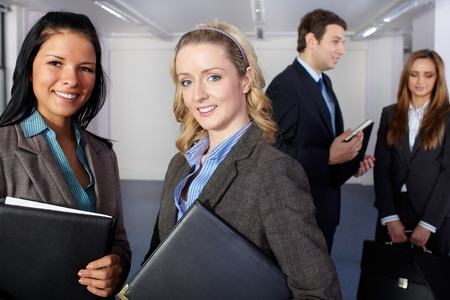 Group of 4 young business people, two females at foreground and two people blurred in the background photo