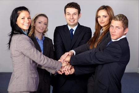 ensemble mains: �quipe de 5 jeunes gens d'affaires et heureux, tient leurs mains