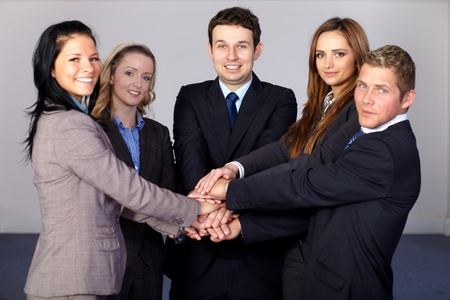 Team of 5 young and happy business people, holds their hands together photo