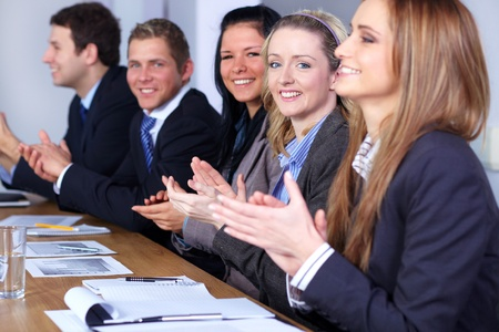 Business team clapping hands during their meeting, focus on blonde smiling female Archivio Fotografico