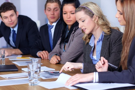 Team of 5 business people working on some calculations, calculator and come documents on conference table, focus on blonde female Stock Photo - 11274319