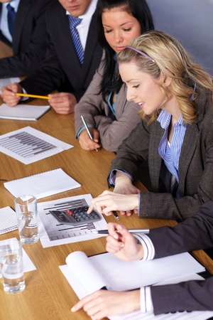Blonde businesswoman and her team sits at conference table and work on some calculations photo