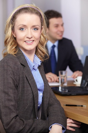 Blonde businesswoman sitting at conference table during business meeting photo