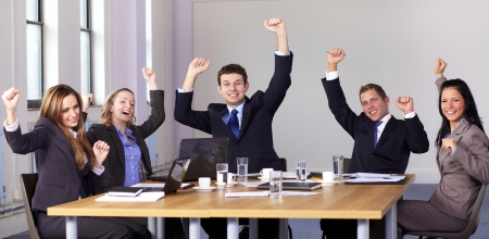 Victory gesture made by 5 business people sitting at conference table