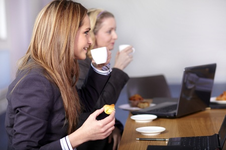 Two businesswoman sitting at conference table have a break during meeting photo