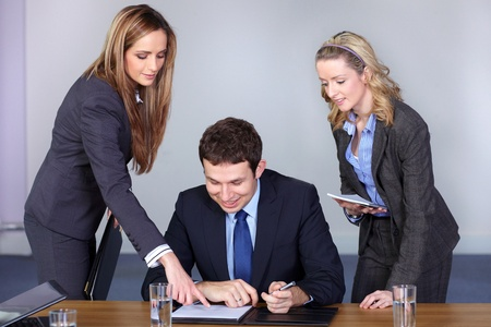 Young businessman and his two attractive female advisors, point something at his paperwork photo