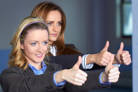 Two Young attractive females in busines suits show thumb up gesture