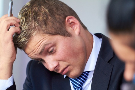 credit crisis: Young worried and stressed businessman scratch his head Stock Photo