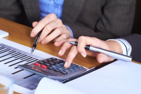 contabilidad financiera cuentas: Dos manos de una mujer con la calculadora y documentación alguna