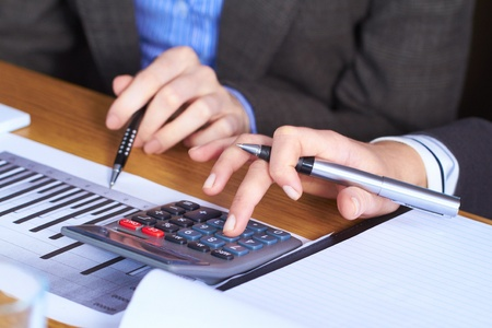 Two female hands with calculator and some paperwork Stock Photo - 11274295