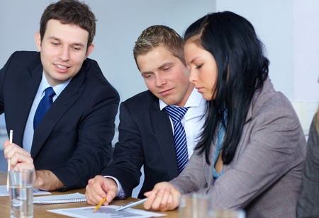 Team of 3 young business people work on some documents, all sitting at conference table Stock Photo - 11274358