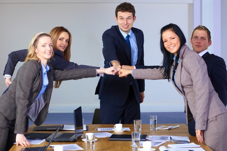 Team of 5 young business people hold their fists together, teamwork and togethernes concept