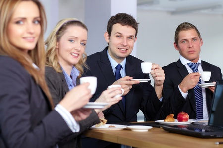 Business team having a coffee break during their meeting, all hold small coffee cups