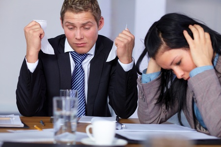 Team of 2 stressed and depressed business people sitting at conference table, negotiation failure or bankrupcy concept