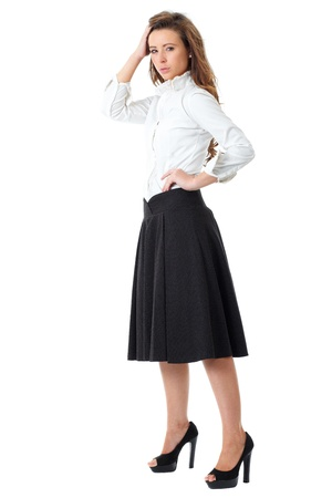 Young atractive female in white shirt and black skirt pose over white background Banque d'images