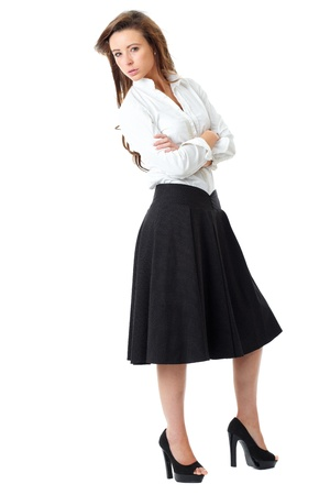 Young atractive female in white shirt and black skirt pose over white background photo
