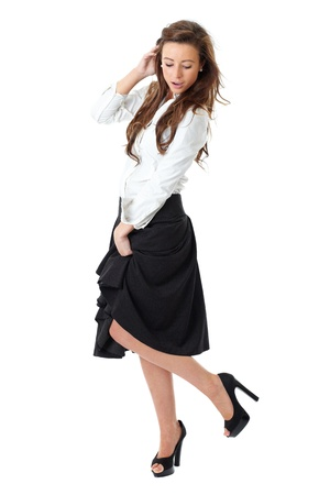 Young atractive female in white shirt and black skirt pose over white background Archivio Fotografico
