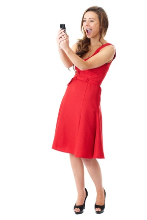 takes: Young happy attractive female in red dress takes photos using her mobile phone, shoot over white background Stock Photo