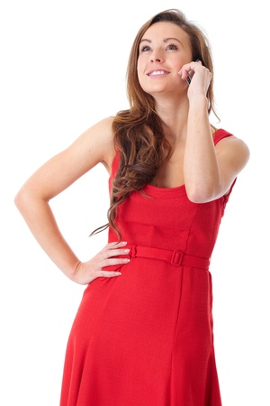 Young happy attractive female in red dress chat over mobile phone, shoot over white background Stock Photo
