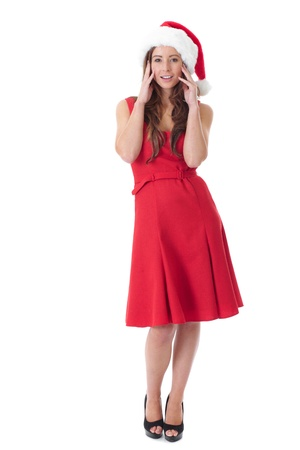 Attractive young brunette girl in red dress and santa hat, isolated over white background photo