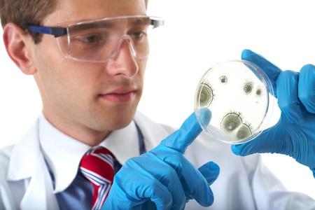 biotecnologia: joven asistente de laboratorio de verificación masculina placa de Petri con agar y la bacteria en él, aislados en blanco Foto de archivo