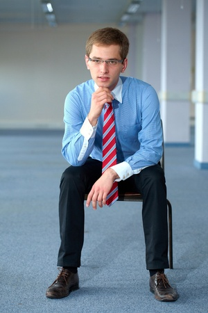 man in chair: Young thoughtful businessman in blue shirt and red tie, office shoot