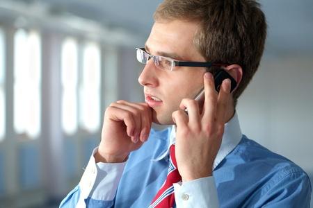 conversa: joven hombre de negocios confidente en camisa azul y corbata roja habla por tel�fono m�vil en su oficina