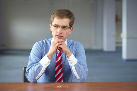 young confident businessman sits at his desk, wears blue shirt and red tie photo