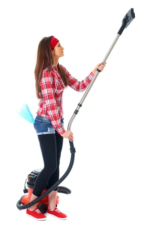 young attractive female cleaner in red shirt use vacuum cleaner, isolated on white photo