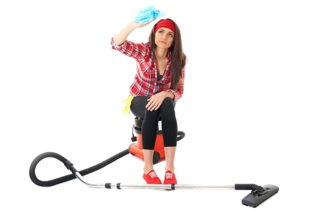 young attractive female cleaner in red shirt sits on vacuum clenaer,  isolated on white background photo